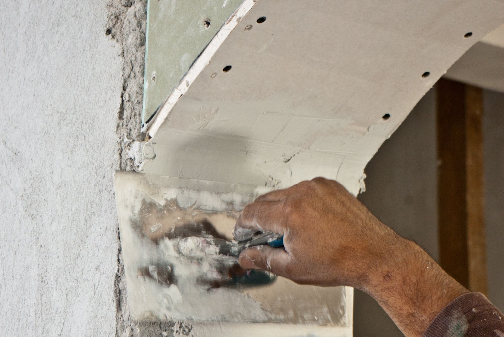 Using a float to apply mud on drywall arch