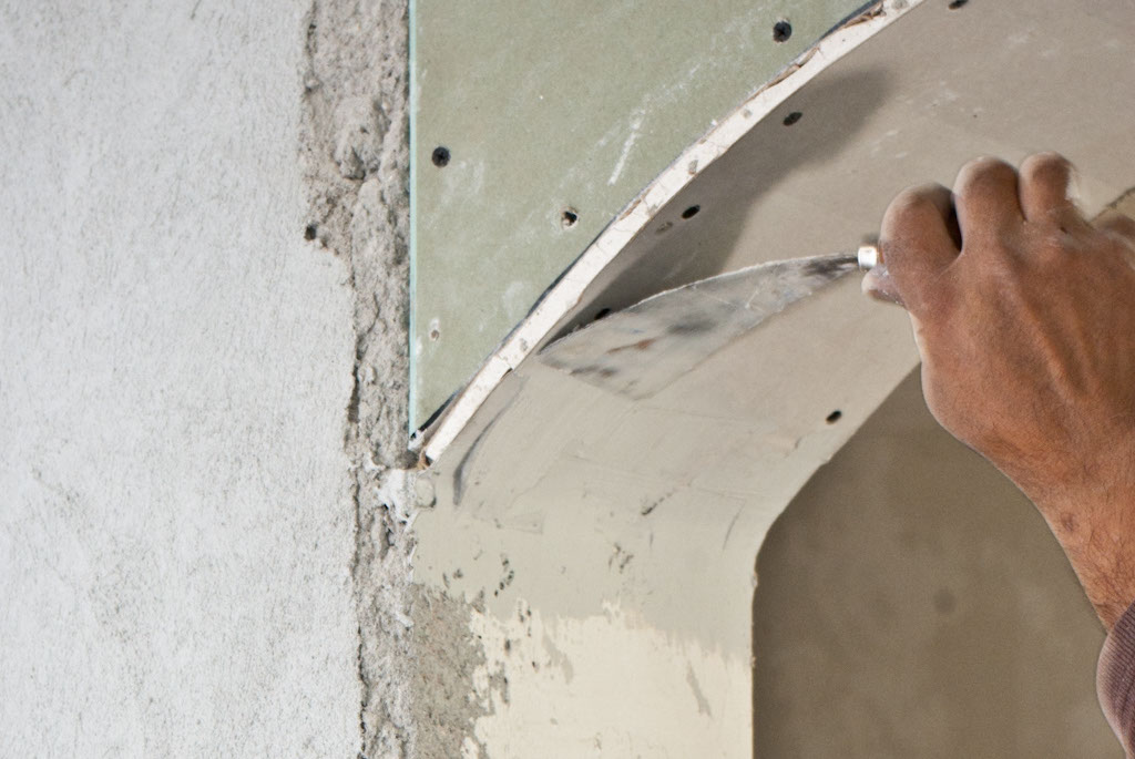 Applying mud with a trowel on the drywall arch