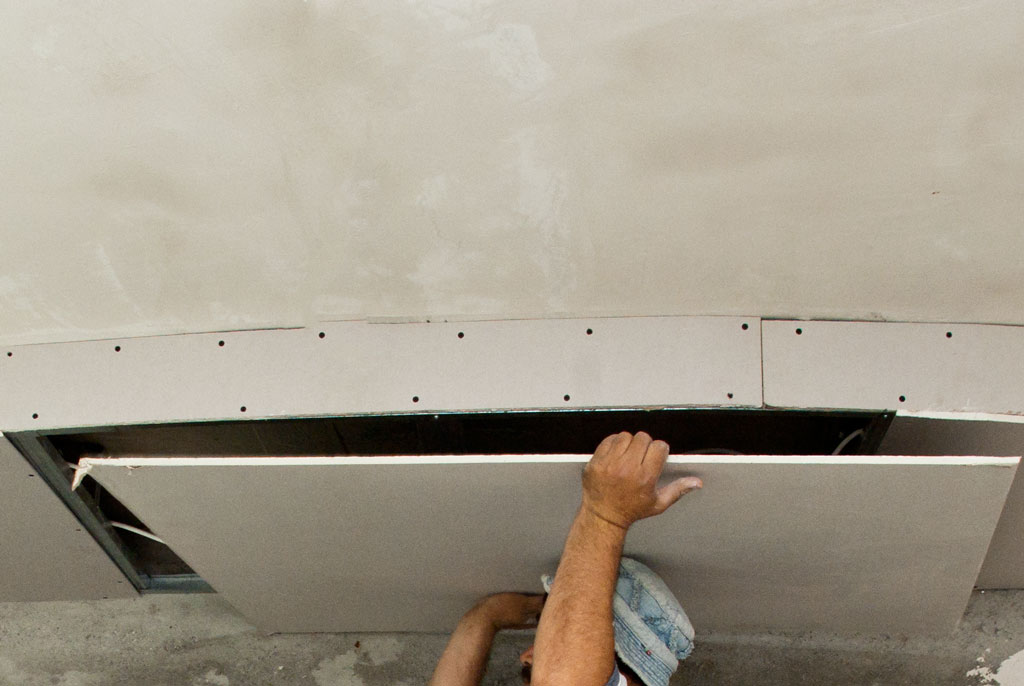 Fixing the last drywall board on the ceiling arch