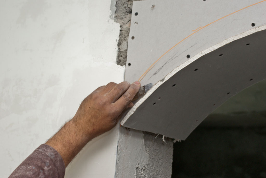 Cutting the excess drywall arch with a razor knife