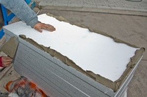 Adding mortar to polystyrene sheets