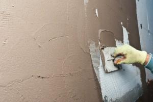 Applying putty over the fiberglass mesh
