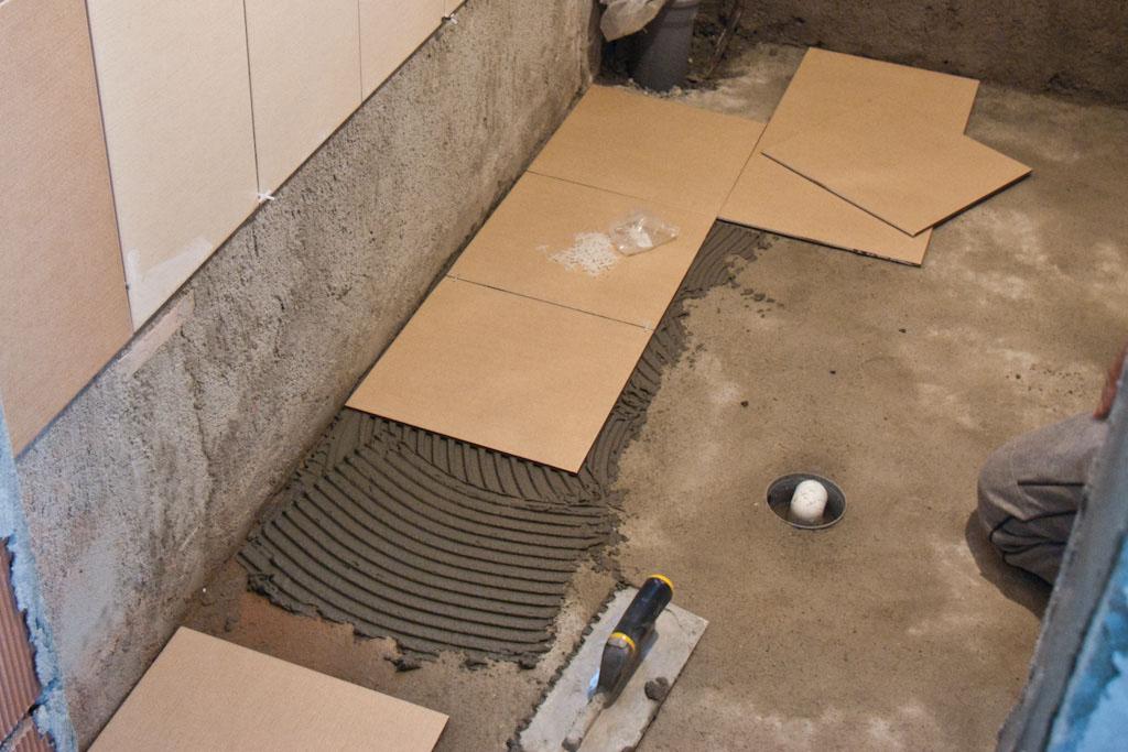 Spreading tile adhesive on floor