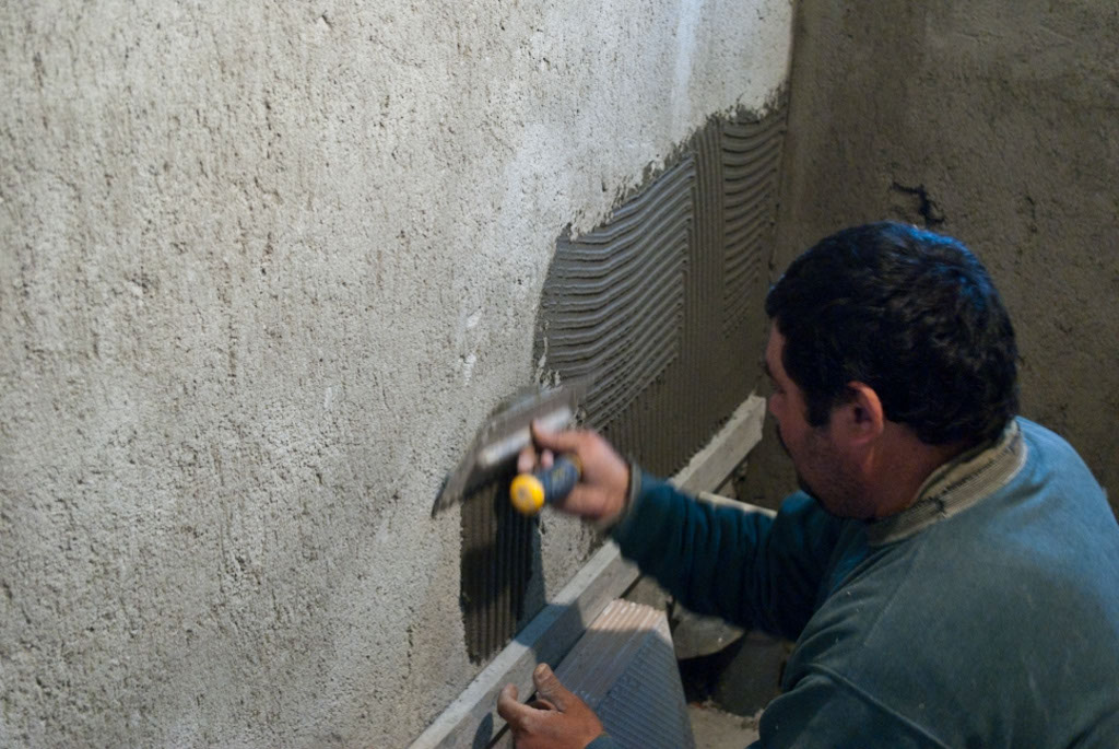 Spreading out adhesive on wall