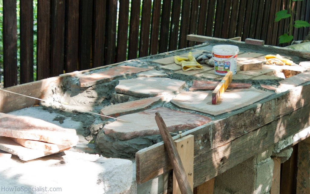 Installing flagstone on the countertop of the outdoor kitchen