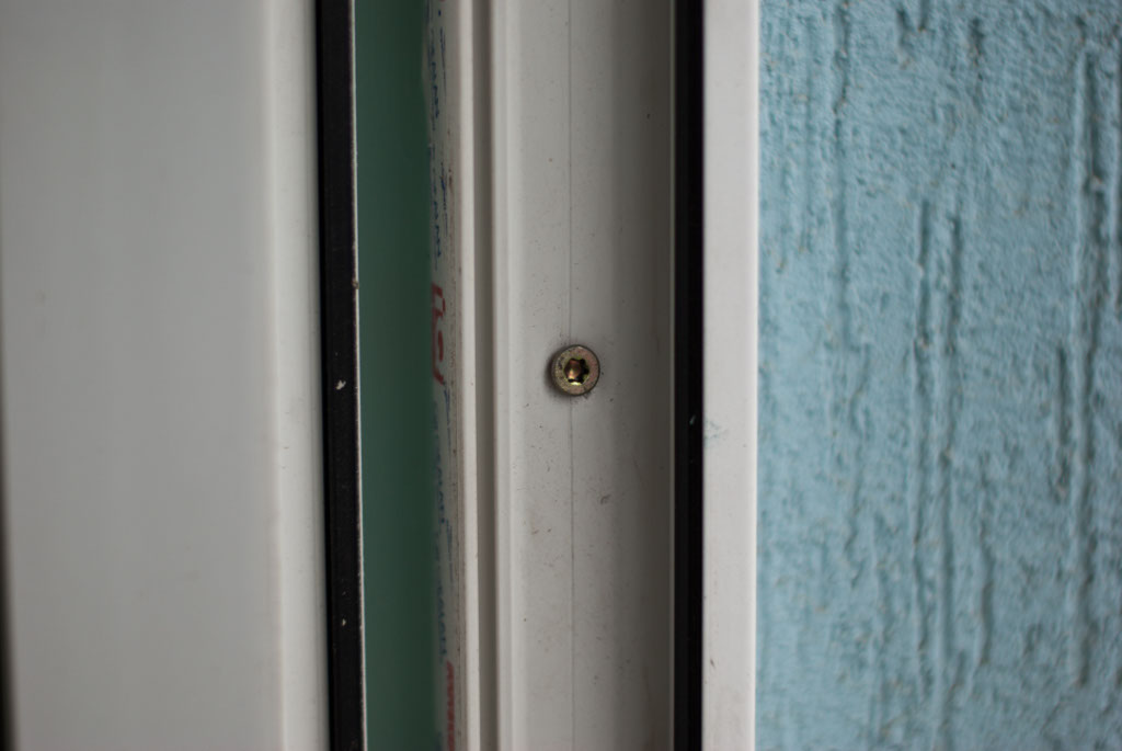 Inserting screws in the PVC window frame