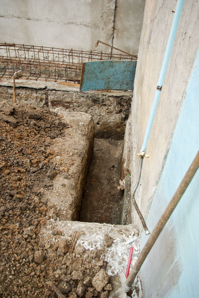 Digging foundation along house