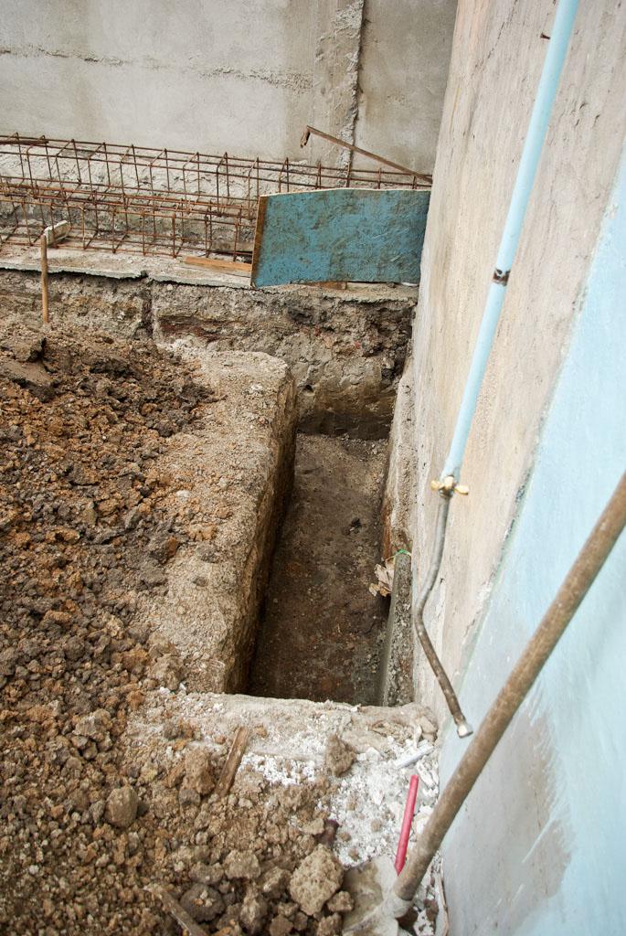 Digging foundation along house