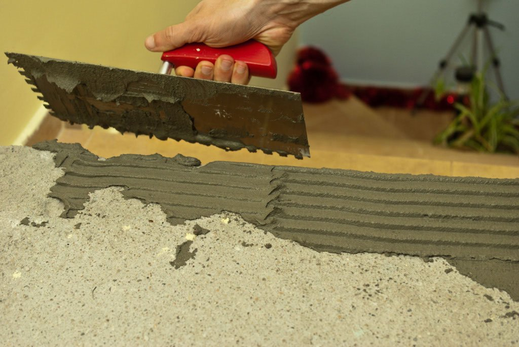 Spreading tile adhesive with a float