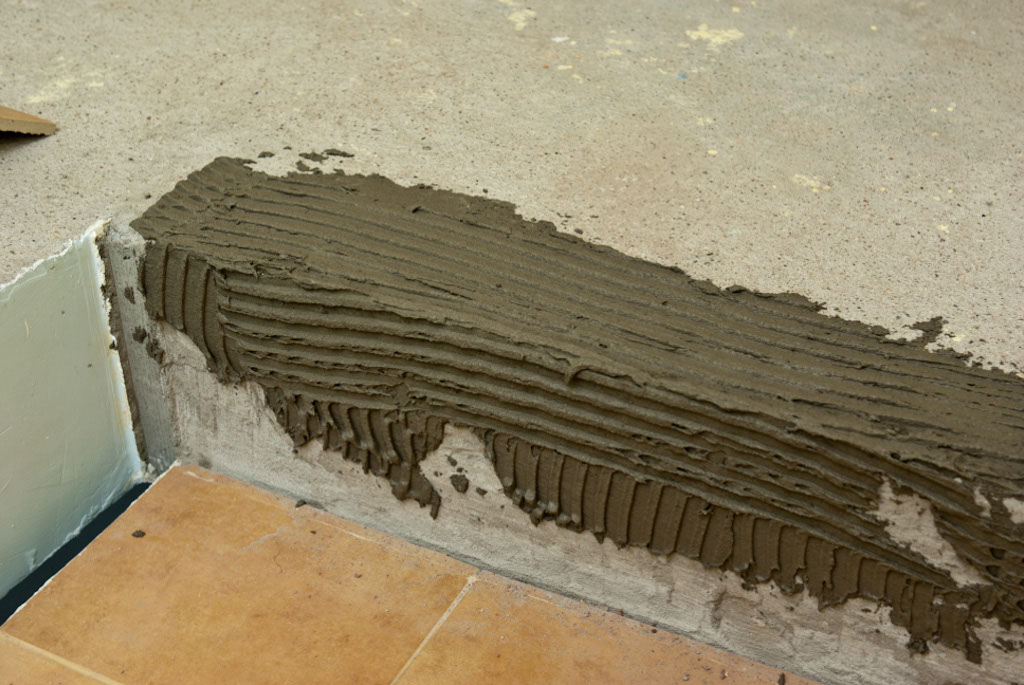 Spreading tile adhesive on stairs
