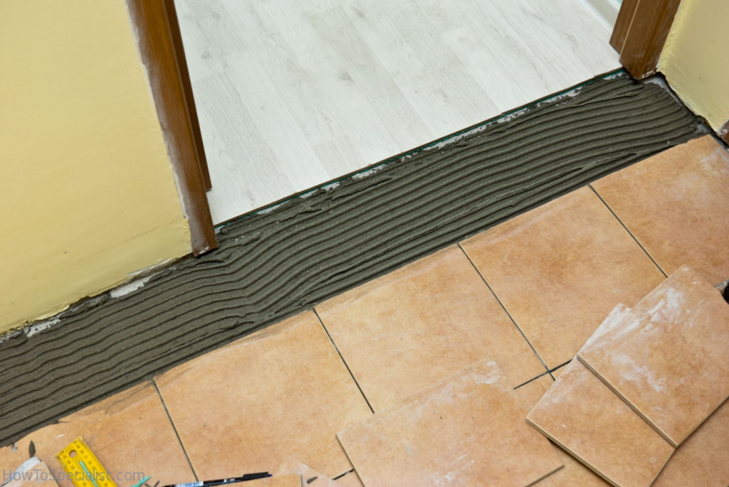 Spreading tile adhesive on floor