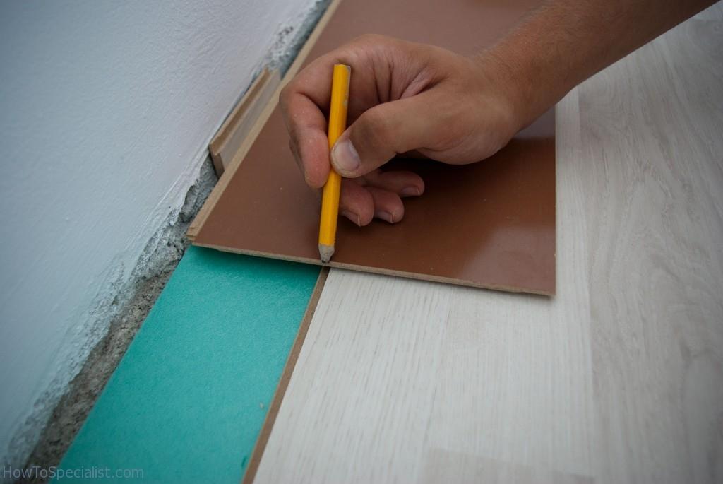Fitting laminate flooring along wall