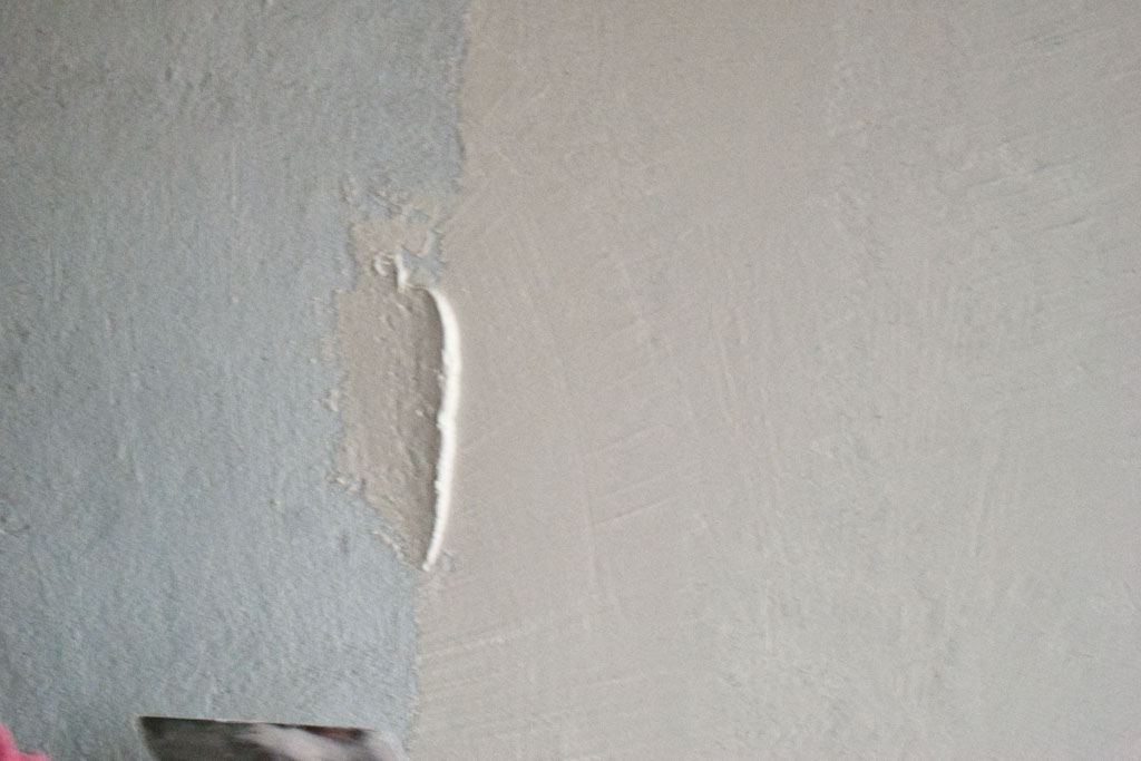Spreading plaster on render