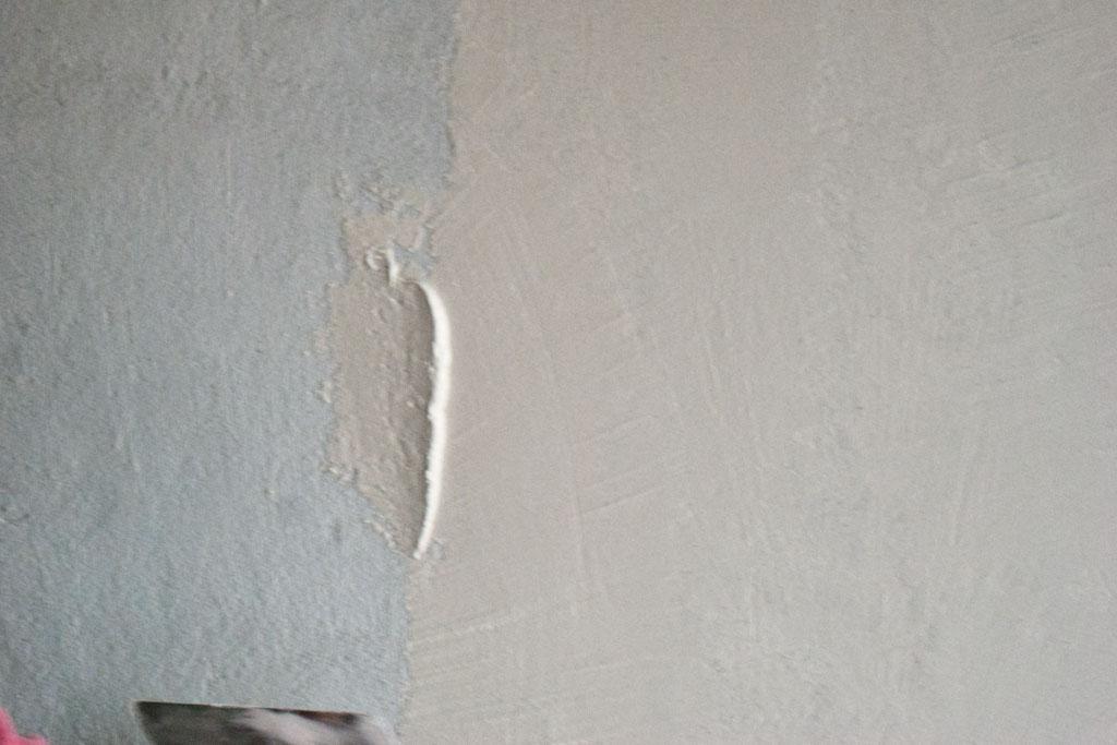 Spreading plaster on render