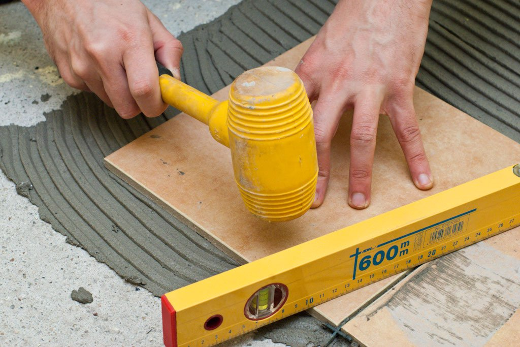Using a mallet to set tiles
