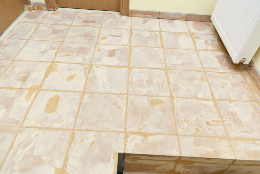 Grouting floor tiles