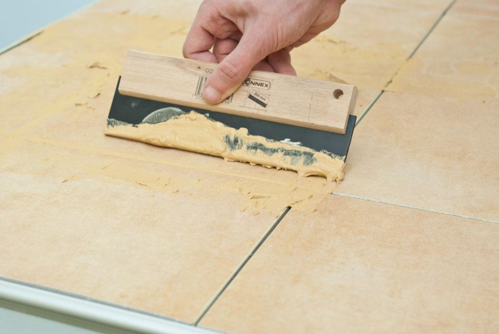 Grouting floor tiles