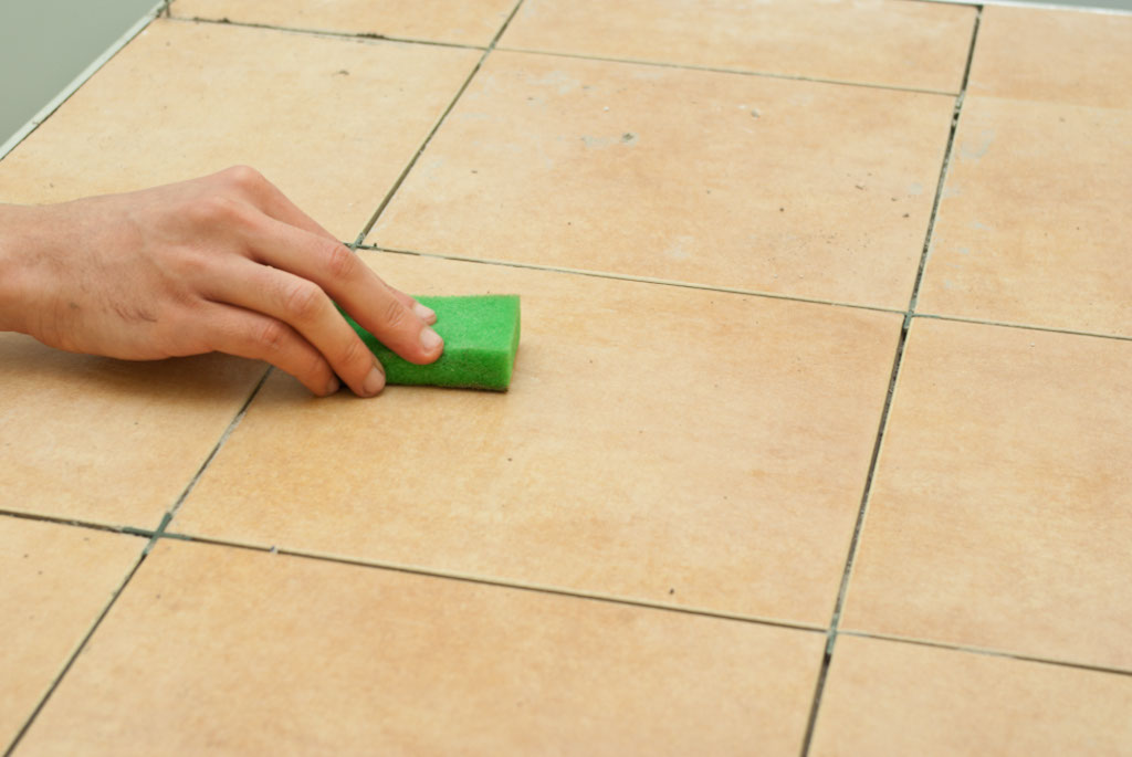 Cleaning tile with a sponge