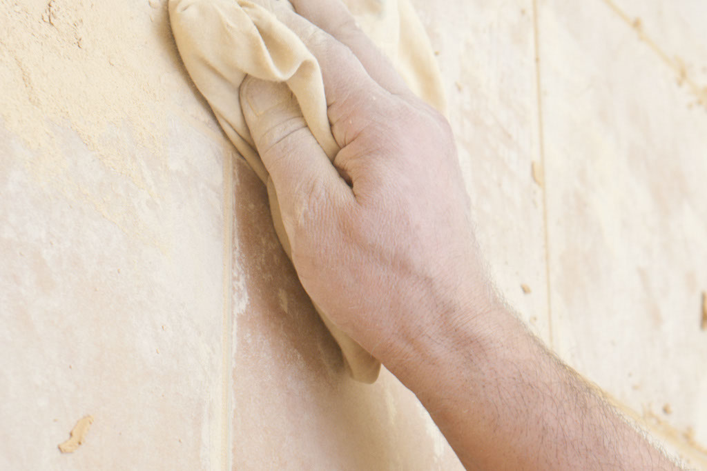 Removing grout off the tiles with a dry cloth